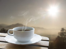 cup-coffee-over-wood-table-sunrise-behind-mountains-58367092